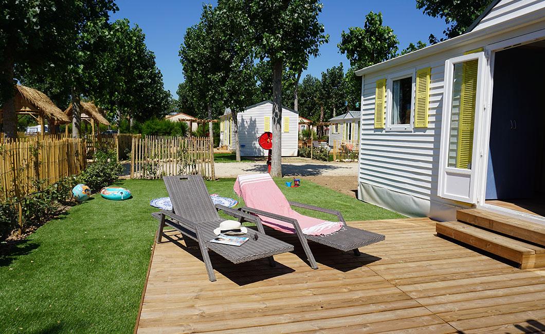 location avec grand espace extérieur terrasse en bois avec mobilier de jardin et paillote