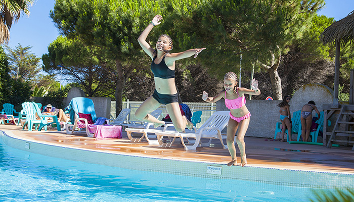 two children dive into the large pool, camping with swimming pool