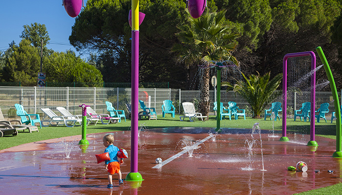 little boy having fun in splashpad, safe aquatic area for children