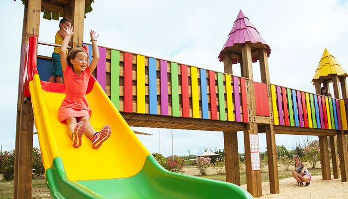 children's area, family holidays, playground in the shape of a castle, made of wood with slides