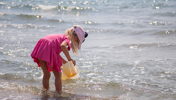 little girl playing in the water at the beach, sand castle, mini club, activity with children