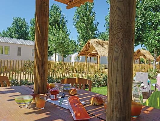 ontbijt in huuraccommodatie camping op gemeubileerd terras met houten tafel en rieten parasol grote tuin